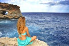 Młoda atrakcyjna kobieta patrzeje dennego horyzont siedzi samotnie na r obrazy stock
