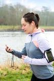 Młoda atrakcyjna kobieta sprawdza chronometru durng bieg se Fotografia Stock