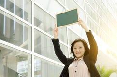 Młoda Azjatycka biznesowa kobieta pokazuje pustego chalkboard Fotografia Stock