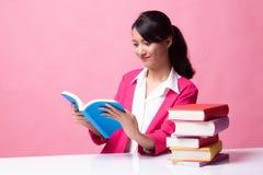 M?oda Azjatycka kobieta czyta ksi??k? z ksi??kami na stole zdjęcia royalty free