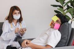 M?oda Azjatycka kobiety lekarka diagnozuje obezw?adniaj?cego zapracowanego biznesowego m??czyzny z schowkiem obraz royalty free