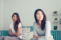 Młoda Azjatycka lesbian para dyskutuje ich plecy i obraca each inny w okresie smutny w sypialni Zdjęcie Stock
