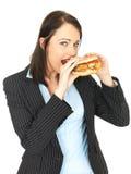 Młoda Biznesowa kobieta Je kurczaka hamburger Obrazy Royalty Free
