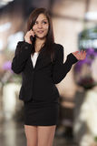 Młoda biznesowa kobieta opowiada na jej telefonie komórkowym. Obrazy Stock