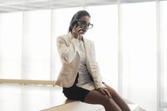 Młoda biznesowa kobieta opowiada telefonem komórkowym w biurze i obsiadaniem na kroku zdjęcia stock