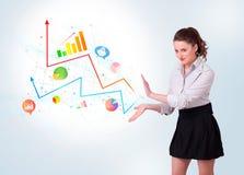 Młoda biznesowa kobieta przedstawia kolorowe mapy i diagramy Fotografia Royalty Free