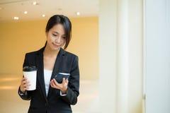 Młoda bizneswomanu mienia kawa i spojrzenie przy telefonem komórkowym Zdjęcia Royalty Free