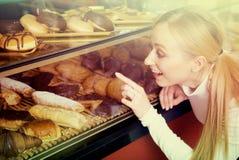 Młoda blond dziewczyna z zadowoleniem wybiera ciasto Obrazy Stock