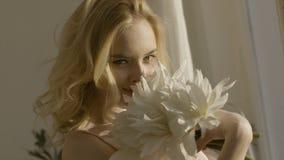 M?oda blondynki kobieta z kwiatami w jej r?kach w s?o?cu akcja M?oda pi?kna kobieta w ?wietle s?onecznym z kwiatami w domu zdjęcia stock