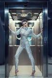 Młoda cyber kobieta w srebnej futurystycznej kostiumowej pozyci w windzie Zdjęcie Royalty Free