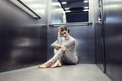 Młoda cyber kobieta w srebnym futurystycznym kostiumowym obsiadaniu w windzie Fotografia Stock