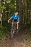 Młoda cyklista jazda w lesie Fotografia Royalty Free
