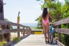 Młoda dama w swimsuit odprowadzeniu z bicyklem dalej Obrazy Stock