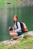 Młoda dama wycieczkowicz z plecaka obsiadaniem na górze Obrazy Royalty Free