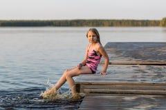 Młoda dziewczyna bryzga jego ciekami w jeziorze Obraz Stock