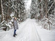M?oda dziewczyna chodzi w zima lesie i cieszy si? cisz? fotografia stock