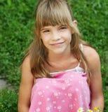 Młoda dziewczyna jest siedzi na gras Zdjęcia Royalty Free