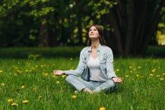 Młoda dziewczyna medytuje w parku Zdjęcie Royalty Free