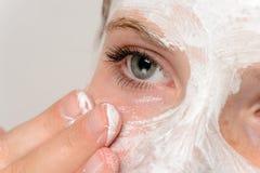 Młoda dziewczyna palce stosuje twarzy maski moisturizer Zdjęcia Stock