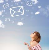 Młoda dziewczyna patrzeje poczta symbol chmurnieje na niebieskim niebie Obrazy Stock