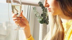 M?oda dziewczyna pije szampa?skiego obsiadanie na pr?towej stolec blisko okno zbiory wideo