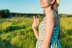 Młoda dziewczyna pokazuje aprobaty gestykuluje outdoors Obraz Royalty Free