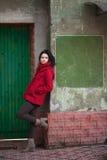 Młoda dziewczyna przy zielonym drzwi Zdjęcia Stock