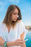 Młoda dziewczyna relaksuje przy dokiem podczas gdy bencel muzyka Obrazy Stock