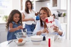 M?oda dziewczyna robi tortowi w kuchni z jej babci?, mum stoi dopatrywanie, selekcyjna ostro?? zdjęcie royalty free