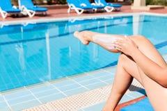 M?oda dziewczyna siedzi basenem i ochrania jej sk?r? z s?o?ce ?mietank? S?o?ce ochrony czynnik w wakacje, poj?cie fotografia stock