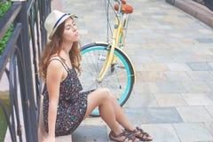 Młoda dziewczyna siedzi blisko rocznika roweru przy parkiem Zdjęcia Royalty Free