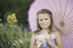 Młoda dziewczyna trzyma parasol w ogródzie Obrazy Royalty Free