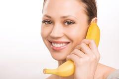 Młoda dziewczyna z bananem obok jej twarzy Obraz Royalty Free