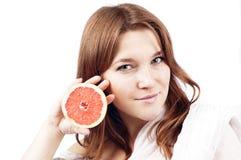 Młoda dziewczyna z grapefruitowy odosobnionym na bielu Obrazy Stock