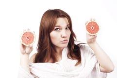 Młoda dziewczyna z grapefruitowy odosobnionym na bielu Fotografia Stock