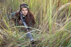 Młoda dziewczyna z karabinowym zerkaniem z trawy Fotografia Royalty Free