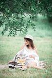 Młoda dziewczyna z kwiatami w lato kapeluszu pozuje na polu Zdjęcia Royalty Free