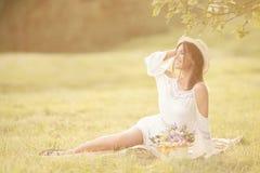 Młoda dziewczyna z kwiatami w lato kapeluszu pozuje na polu Zdjęcie Royalty Free