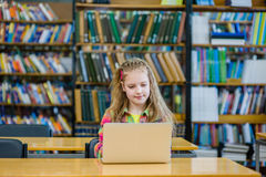 Młoda dziewczyna z laptopem pracuje w bibliotece Obrazy Royalty Free