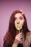 Młoda dziewczyna z lizakiem na menchii Fotografia Stock