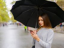 Młoda dziewczyna z telefonem komórkowym na ulicie i parasolem obrazy royalty free