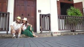 M?oda elegancka para w s?omianych kapeluszach siedzi na progu zdjęcie wideo