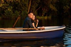 M?oda europejska para jest wodniactwo na jeziorze, m?ody cz?owiek i jego dziewczyna siedzi w ??d? przy zmierzchem, para w mi?o?ci fotografia royalty free