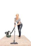 Młoda gospodyni domowa vacuuming dywan Obrazy Stock