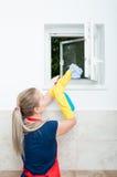 Młoda gospodyni domowa wyciera okno Zdjęcie Stock