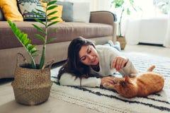 M?oda kobieta bawi? si? z kotem na dywanie w domu Mistrzowski lying on the beach na pod?odze z jej zwierz?ciem domowym obrazy stock