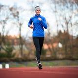 Młoda kobieta bieg przy śladem Obraz Stock