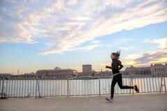 Młoda kobieta bieg w zmierzchu Zdjęcia Stock