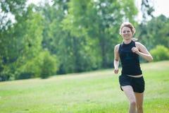 Młoda kobieta biega przy parkiem Fotografia Royalty Free