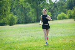 Młoda kobieta biega przy parkiem zdjęcie stock